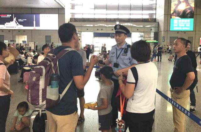 ↑民警向带小孩的家长宣传安全常识。