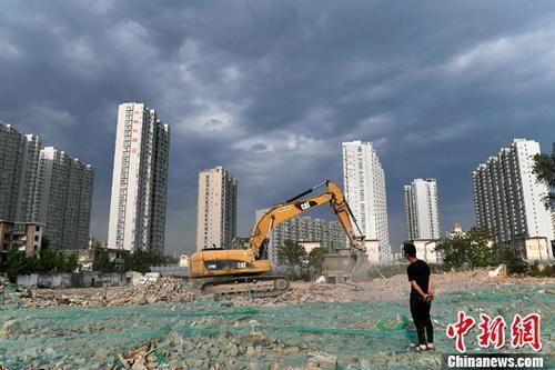 资料图:工人操作挖掘机在太原一商品房建设工地施工作业。中新社记者 韦亮 摄