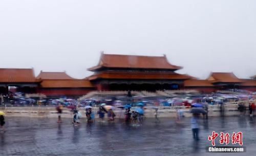 资料图:7月17日,北京连日降雨,游客在北京故宫游览兴致不减。中新社记者 杜洋 摄