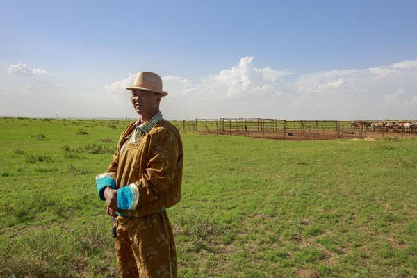 牧民苏 呼格吉勒图站在自家马场前眺望远方