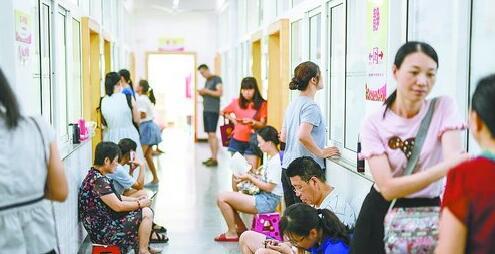 不少家长坐着小板凳等孩子下课