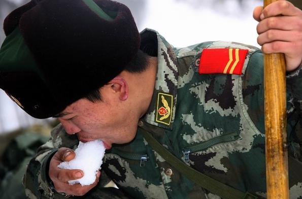 2008年2月3日,一名武警战士在京珠高速公路破冰铲雪间隙吃雪解渴。(来源:新华社)