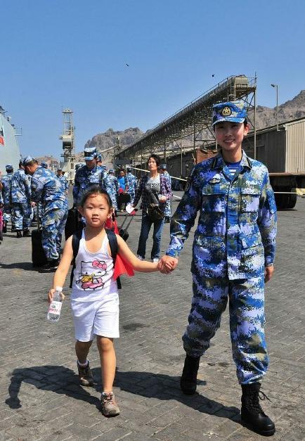 2015年3月,也门,海军女战士牵着一名小女孩的手准备登上军舰。