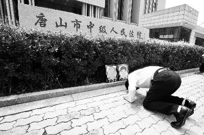 廖海军给父母遗像下跪。