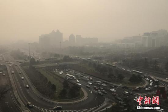 资料图:雾霾中的北京建国门桥地区。中新社记者 李慧思 摄