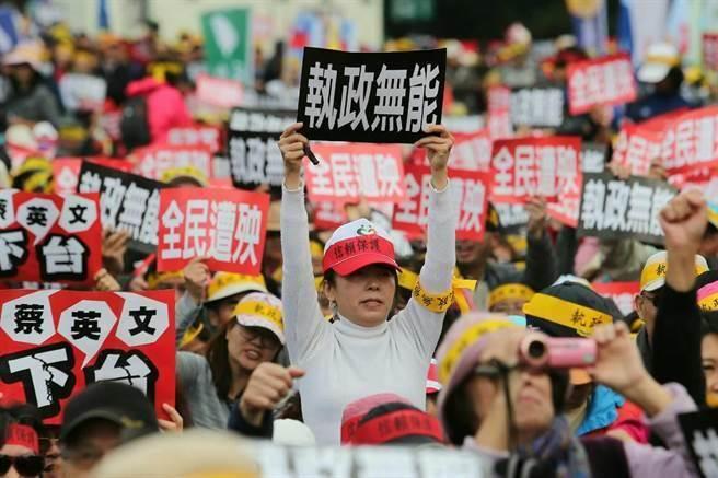 图为反年金改革的军公教人员手持标语表达愤怒。