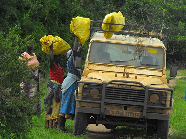 Women who are central suppliers in the bushmeat trade loading their bushmeat packed in Yellow and White sacks on to a tourist vehicle in Murchison Falls National Park. (Photo/Timothy Sibasi)