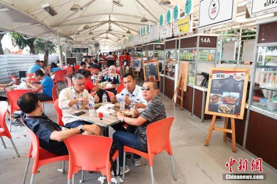 在雅加达亚运会美食街大排档觅食的各国记者和游客。 中新社记者 刘关关 摄