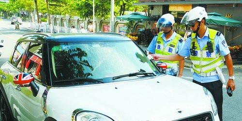 骑警给违停车辆贴单。