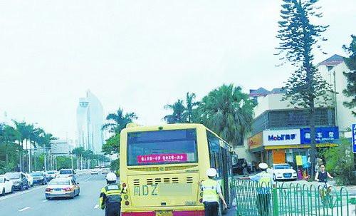 骑警推动抛锚的公交车。