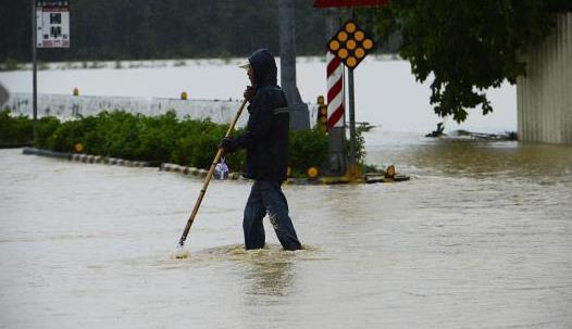资料图:台湾民众在被雨淹没的马路出行。刘震 摄