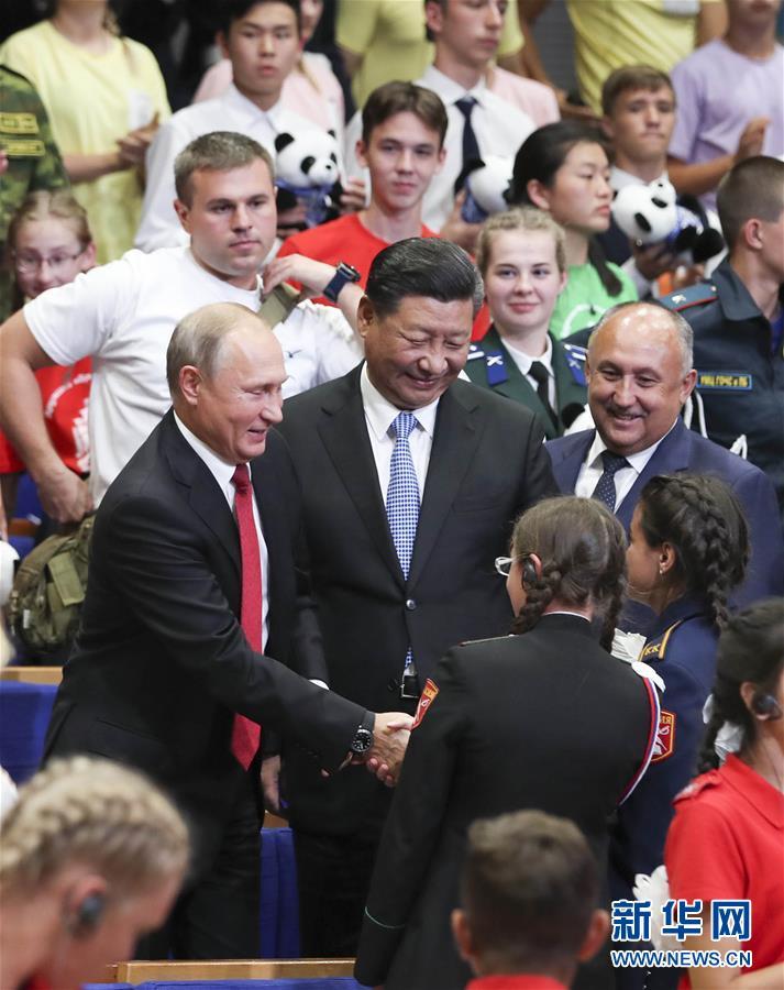 """9月12日,国家主席习近平在符拉迪沃斯托克同俄罗斯总统普京一起访问""""海洋""""全俄儿童中心。这是习近平和普京在""""海洋""""全俄儿童中心接待汶川地震灾区儿童10周年纪念仪式上同孩子们亲切交谈。"""
