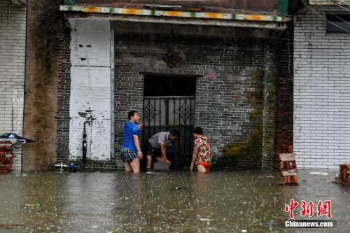 9月17日,广东江门台山大江镇侨园新村,民众使用铁板抵挡家门口的积水。中新社记者 陈骥旻 摄