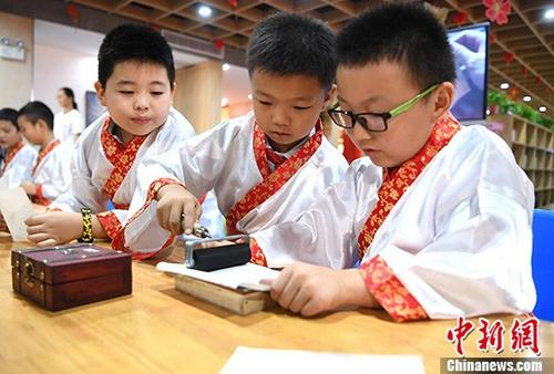 资料图:身穿汉服的小学生在老师的指导下体验活字印刷术。 中新社记者 韩苏原 摄