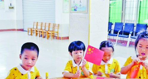 孩子们正在制作小小国旗,培养爱国情操。