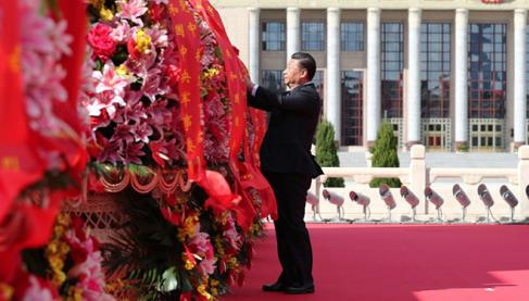 9月30日上午,习近平等党和国家领导人来到北京天安门广场,出席烈士纪念日向人民英雄敬献花篮仪式。这是习近平整理花篮上的缎带。图片来源:新华社