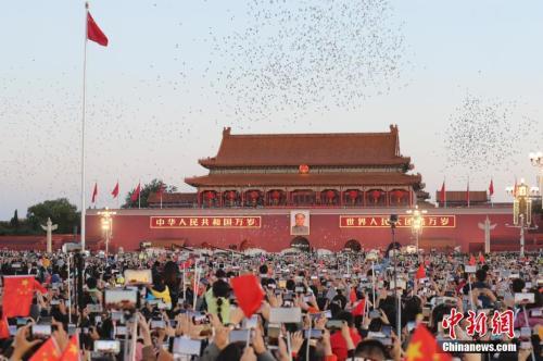 10月1日,来自中国各地的民众特意来到天安门广场观看升旗仪式并唱响国歌,为祖国母亲庆祝生日。中新社记者 盛佳鹏 摄