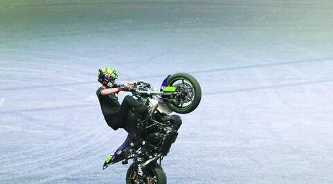 驾驶摩托车进行前轮悬空表演。