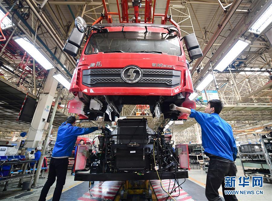 工人在陕重汽汽车总装配厂车间内操作驾驶室吊具,将驾驶室与底盘进行连接(3月15日摄)。新华社记者 邵瑞 摄