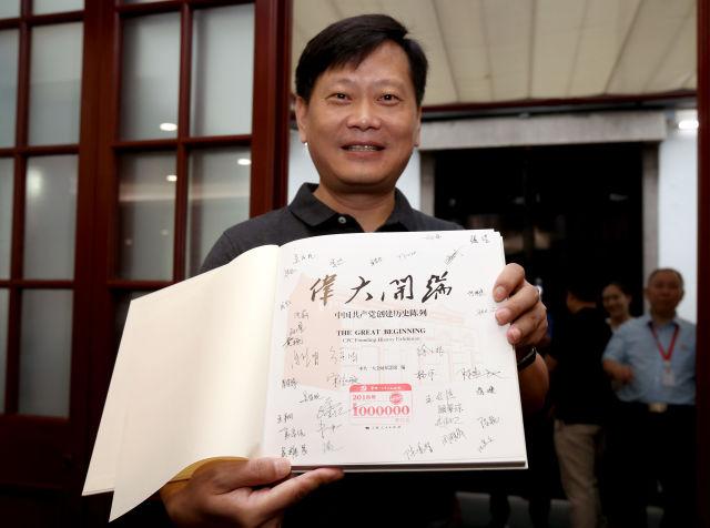 """在中共一大会址纪念馆内,今年的第100万名观众刘凯在展示获赠的精装图册《伟大开端》(8月25日摄)。图册扉页上盖有""""第1000000名观众""""纪念章,还有纪念馆全体工作人员的签名。新华社记者 刘颖 摄"""