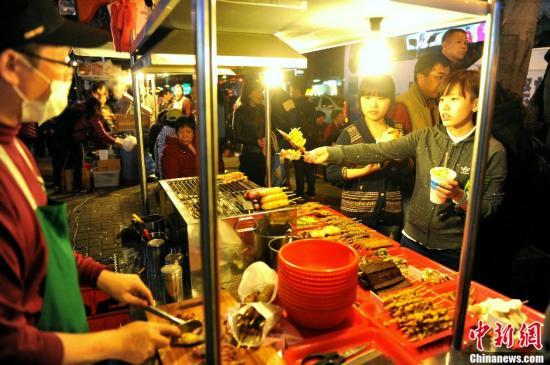 资料图:大陆游客在台北士林夜市品尝美食。中新社发 王东明 摄