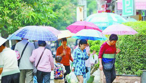 昨日上午的小雨带来些许秋意,图为雨中行人。