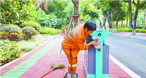 ▲环卫工人认真清洁垃圾桶。