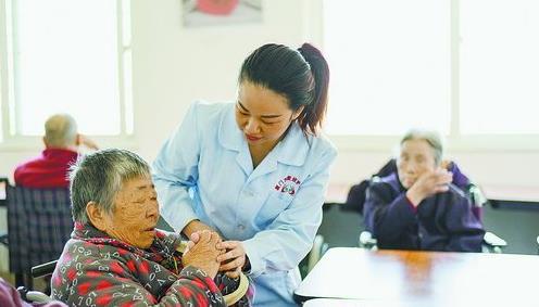 集美爱欣老年公寓里,护理人员照顾老人。