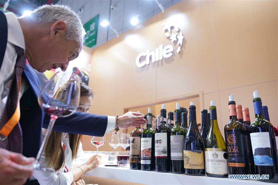 A man looks at wine from Chile at the first China International Import Expo in Shanghai, east China, Nov. 5, 2018.