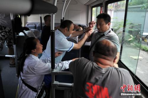 """资料图:2014年7月16日下午,北京公交总队718路公交车总站举行""""反恐演习""""。图为公交车司机、售票员和乘客一同制服""""嫌疑人""""。 中新网记者 金硕 摄"""