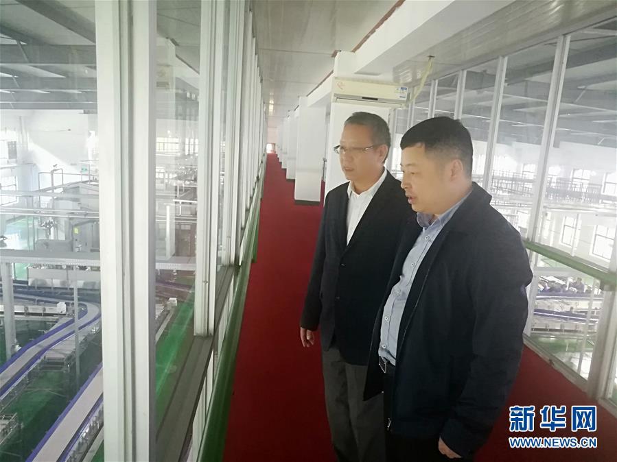 何张辉(右)在饮用水企业调研问需