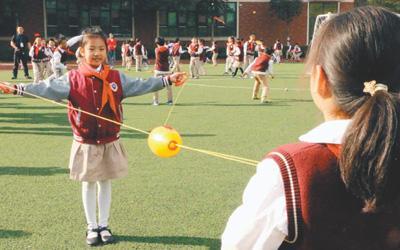 """武汉市红领巾学校学生在操场上分组玩""""穿梭拉拉球""""游戏。"""