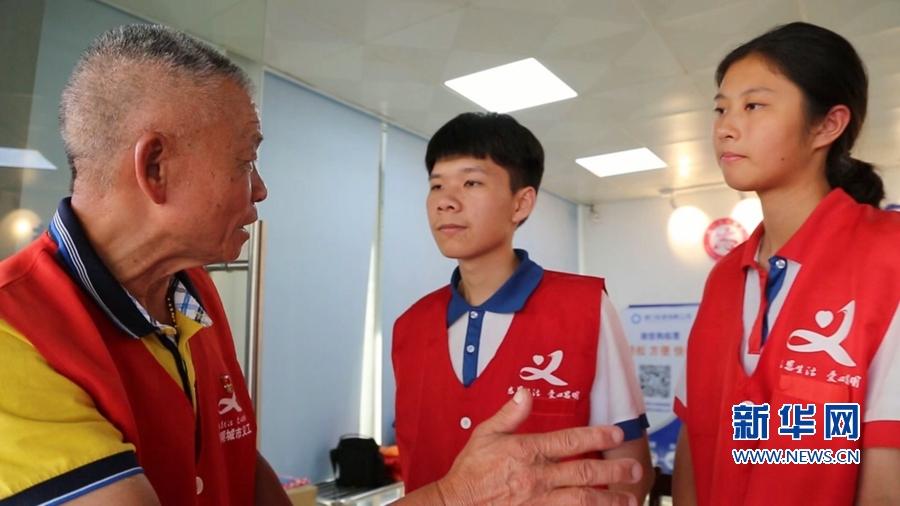 蓝永生向年轻志愿者传授服务经验。新华网发(李文澜 摄)