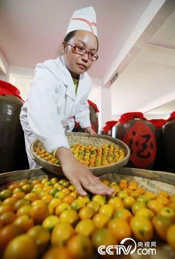 生产车间,一名工人在分拣金桔,准备酿制金桔酒。(谭凯兴 摄)
