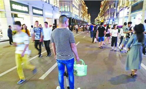 在中山路步行街,一名男子骑着电动平衡车穿梭于拥挤的人群中,十分危险。