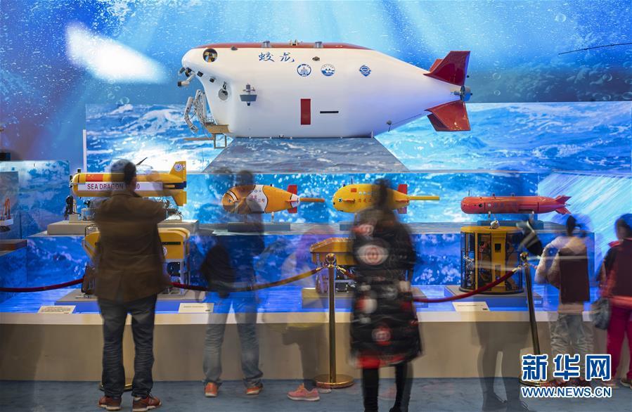 """11月18日,观众在观看""""蛟龙""""号载人潜水器等模型(慢门拍摄)。""""伟大的变革——庆祝改革开放40周年大型展览""""11月13日在国家博物馆隆重开幕。自开幕以来,展览吸引了众多参观者。新华社记者 才扬 摄"""
