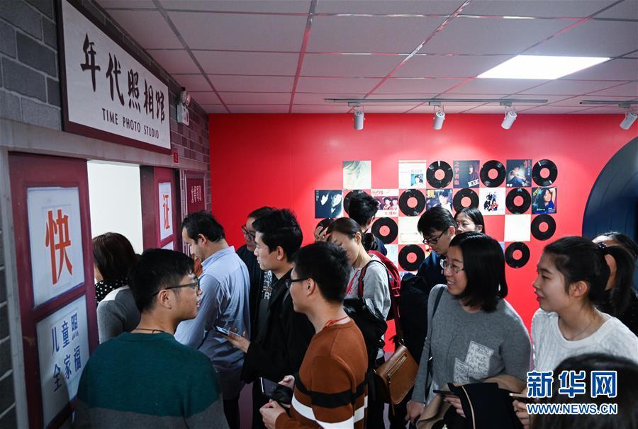 """11月17日,观众在展览上的""""时光博物馆""""内排队体验年代照相馆。 新华社记者 陈晔华 摄"""