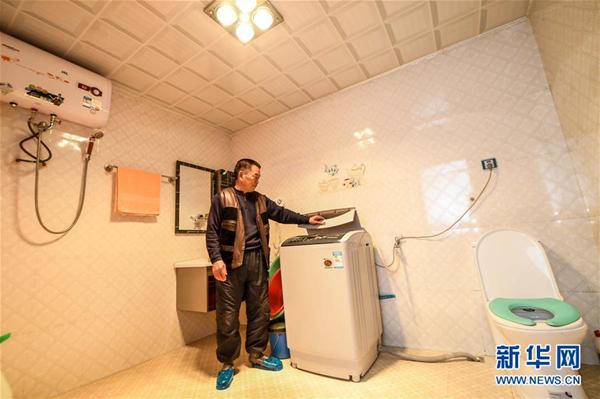 2017年1月24日,吉林延边光东村村民全得成在自家卫生间内使用洗衣机。