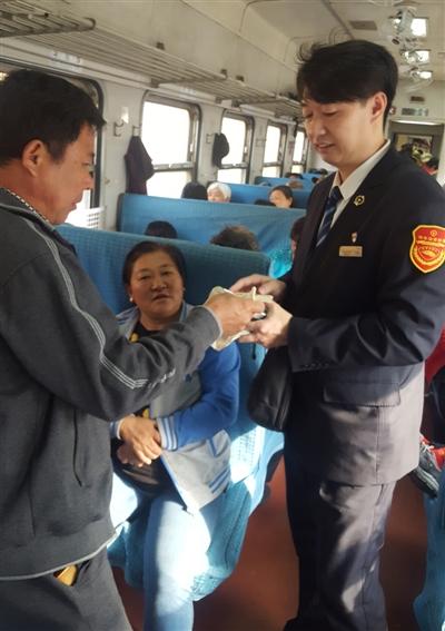 目前,除了四个大站提供售票服务外,7053次经过的其他20个小站都是上车补票。图为列车员正在为乘客补票。