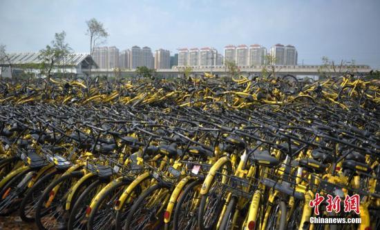 6月7日,成都一停车场内堆放了不少共享单车,大多数车锁已被拆除,这些单车系临时回收、维修中转车辆。中新社记者 刘忠俊 摄
