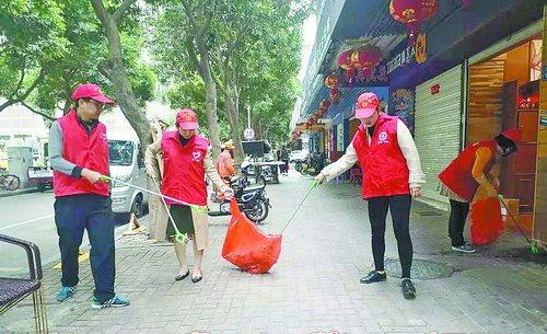 """践行""""路长制"""",志愿者们走上街头,清理路面垃圾。"""