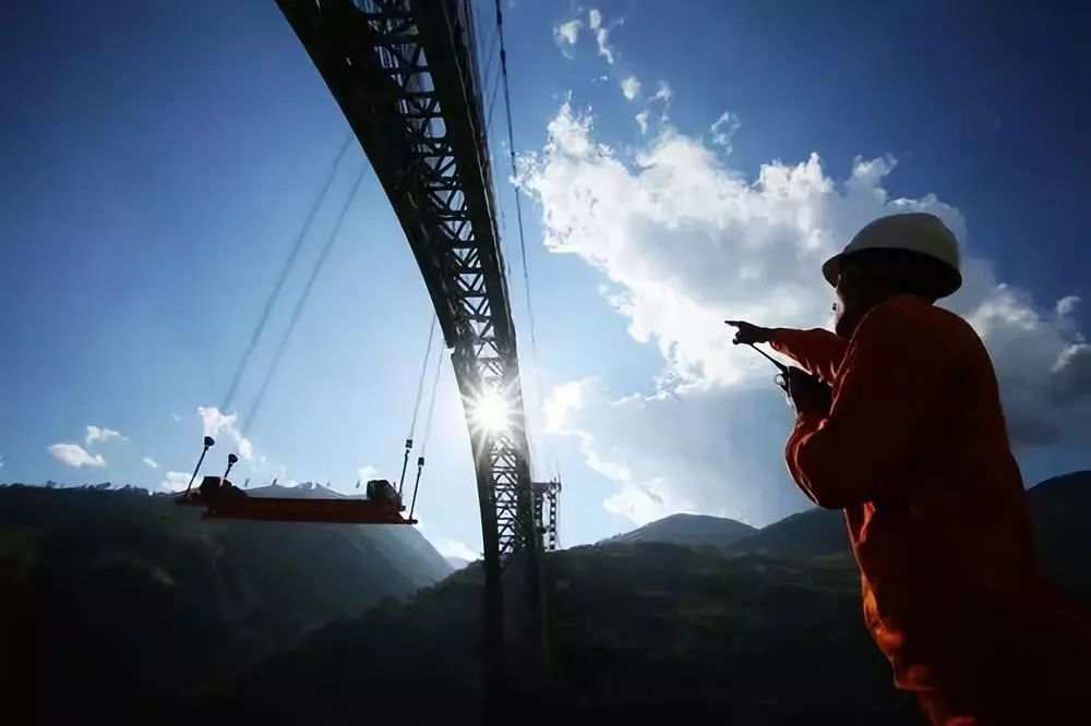 中铁十八局技术人员指挥钢杆件吊装。(图片来源:新华网 伍振 摄)