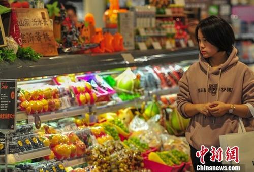 资料图:一名消费者在超市选购商品。中新社记者 于海洋 摄