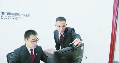 """湖里法院殿前法庭负责人姚亮(右)及法官助理肖安定在调试互联网""""微法庭""""。目前湖里法院已在殿前法庭升级改造全在线法庭和线上线下同步法庭各1处、办公室""""微法庭""""2处。"""