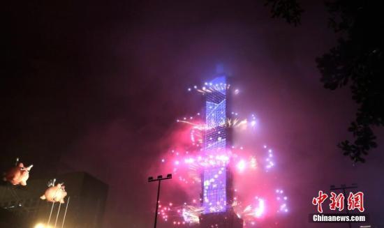 2019年1月1日零时,数以万计的台湾民众与海内外游客冒雨在台北信义区观赏101大楼烟火表演,迎来新年。中新社记者 刘舒凌 摄