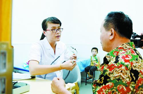 高雪梅在龙湖花园小区卫生服务站给小区居民看诊。