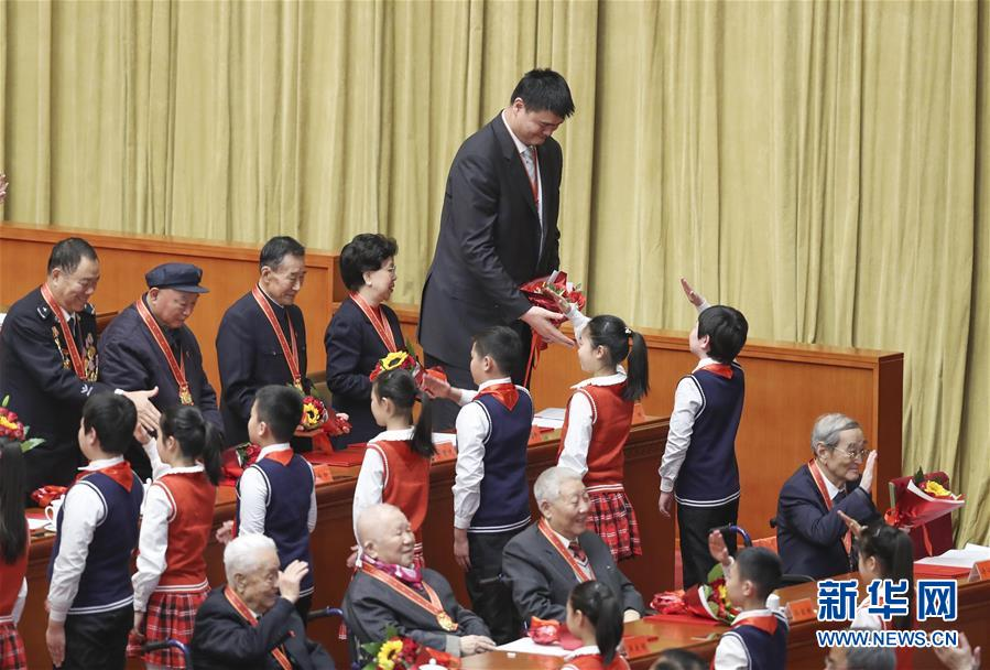 在北京举行的庆祝改革开放40周年大会上,姚明(上)接受少先队员献花(2018年12月18日摄)。新华社记者 殷刚 摄