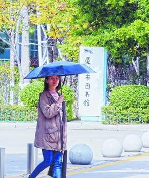 昨日天气温暖如春。图为市民带伞出行