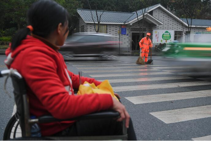 ↑1月9日,董锦香坐着轮椅望着在清扫路面的董基东。