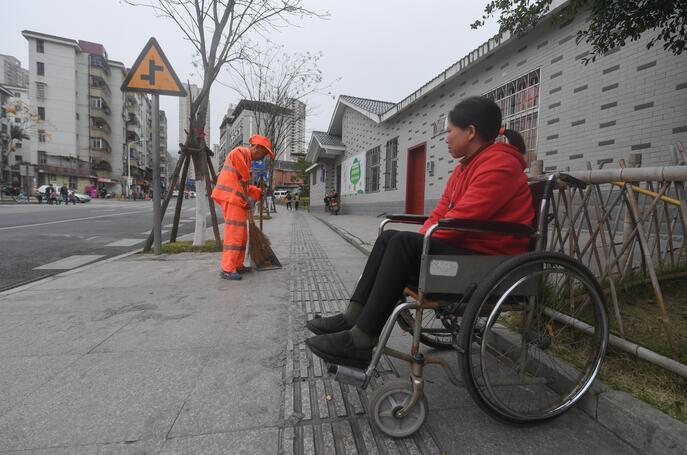 ↑1月8日,董锦香坐着轮椅陪丈夫董基东清扫路面。